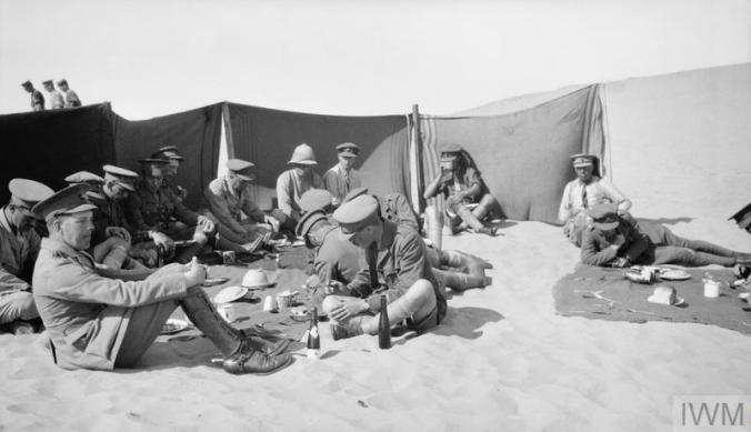 © IWM (Q 57819) men sheltering from sand and having lunch