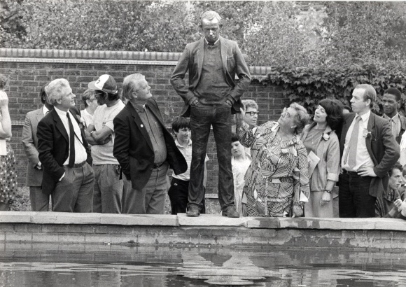 Black and white photograph of the 'Upon Reflection' statue. It is a bronze image of Philip Noel-Baker with his hands in his pockets looking down into a pond. The statue is surrounded by people looking up at it.
