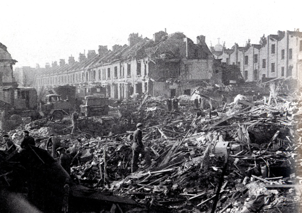 A black and white image of boothby Road after the attack. People are walking through rubble. Many houses are completely destroyed.